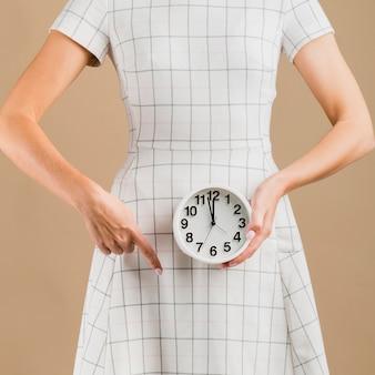 Frau im weißen kleid, das ihre menstruationsperiode zeigt