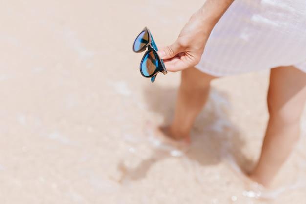 Frau im weißen kleid, das im wasser am resort steht. foto des gegerbten weiblichen modells, das sonnenbrille in der hand hält.
