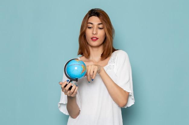 Frau im weißen kleid, das kleinen globus hält