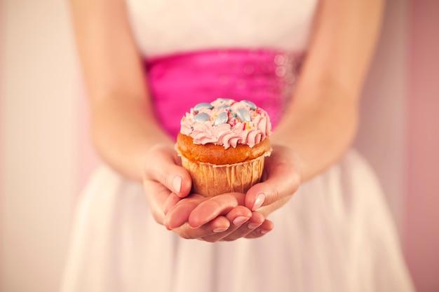Frau im weißen kleid, das rosa muffin hält