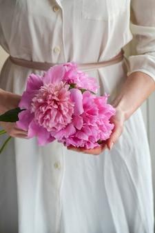 Frau im weißen kleid, das rosa pions pfingstrosenblumen hält. nahansicht