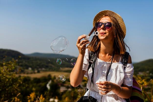Frau im weißen kleid, das seifenblasen bildet