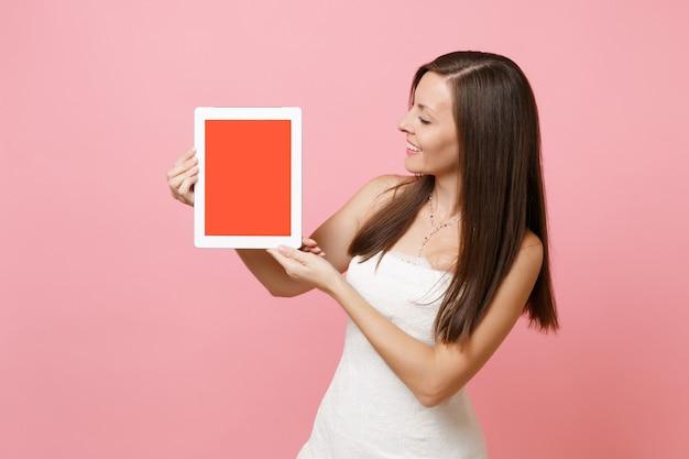 Frau im weißen kleid, die auf einem digitalen tablet mit leerem schwarzen leeren bildschirm beiseite schaut