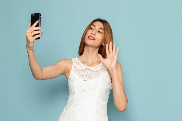 Frau im weißen kleid hält telefonfrau