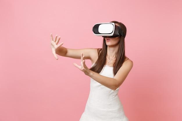 Frau im weißen kleid, headset der virtuellen realität, etwas wie knopf drücken oder auf schwebenden virtuellen bildschirm zeigen