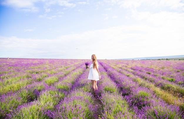 Frau im weißen kleid im feld des lavendels mit blumenstrauß