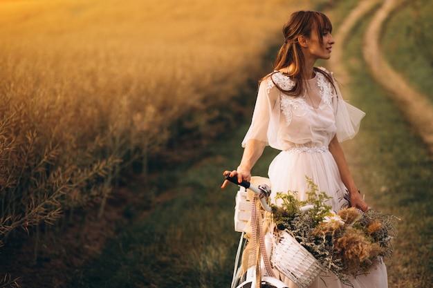 Frau im weißen kleid mit fahrrad auf dem gebiet