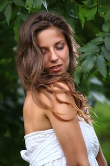 Frau im weißen kleid mit lockigen locken