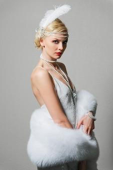 Frau im weißen kleid mit schultergurten und langer pelzboa