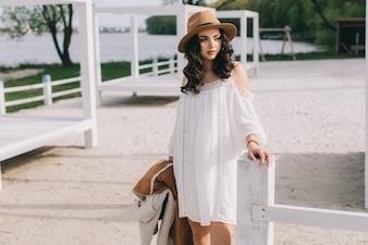 Frau im weißen kleid nahe zaun