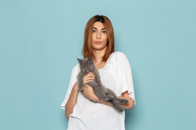 Frau im weißen kleid posiert mit grauem niedlichem kätzchen