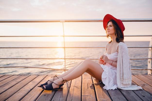 Frau im weißen kleid sitzt am meer auf sonnenaufgang in der romantischen stimmung, die roten hut trägt