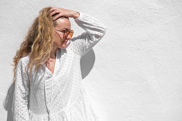 Frau im weißen kleid und in der orange sonnenbrille auf weißem steinmauerhintergrund