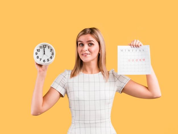 Frau im weißen kleid zeigt uhr und kalender