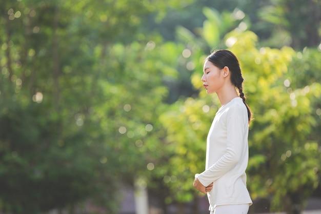 Frau im weißen outfit, das in der natur meditiert