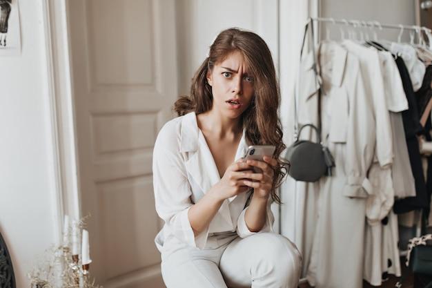 Frau im weißen outfit hält telefon und sieht schockiert aus
