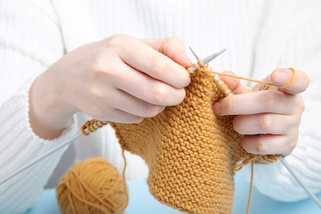 Frau im weißen pullover, der gelbe garnkleidung strickt