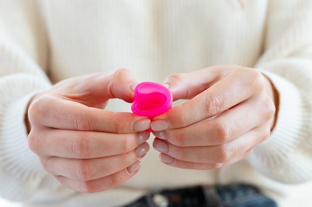 Frau im weißen pullover, der rosa menstruationstasse in den händen nah hält