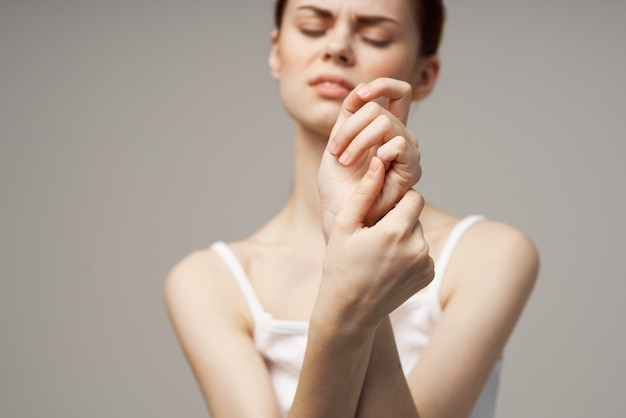 Frau im weißen t-shirt armschmerzen arthritis chronische krankheit heller hintergrund. foto in hoher qualität