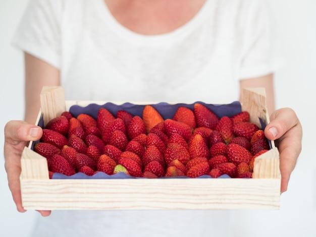 Frau im weißen t-shirt, das holzkiste voll reife erdbeeren hält