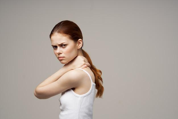 Frau im weißen t-shirt, das sich an den nackengesundheitsproblemen festhält, gemeinsamer heller hintergrund