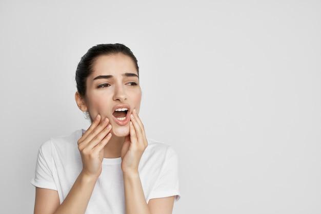 Frau im weißen t-shirt, die gesichtszahnschmerzen-zahnheilkundebehandlung hält
