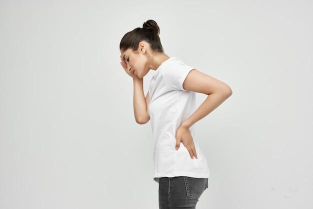 Frau im weißen t-shirt, die ihre gesundheitsprobleme im unteren rücken festhält