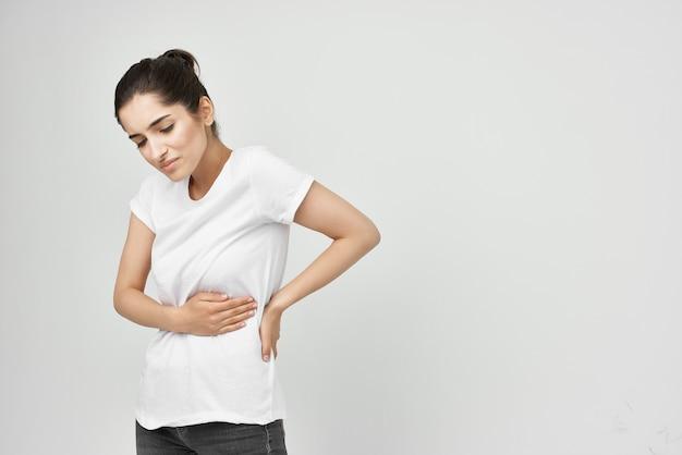 Frau im weißen t-shirt, die ihren bauch hält gesundheitsprobleme bauchschmerzen