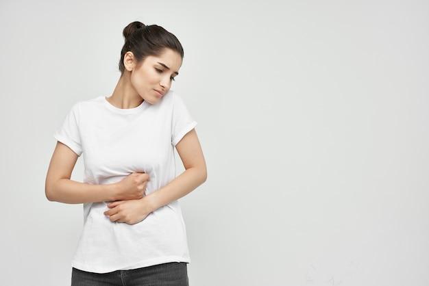 Frau im weißen t-shirt, die ihren magen hält gesundheitsprobleme durchfall bauchschmerzen