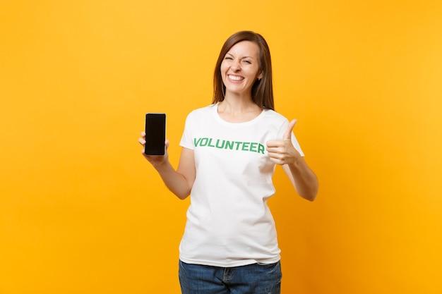 Frau im weißen t-shirt geschrieben inschrift grüner titel freiwilliger halten handy mit leerem bildschirm isoliert auf gelbem hintergrund. freiwillige kostenlose hilfe, konzept der wohltätigkeitsarbeit.