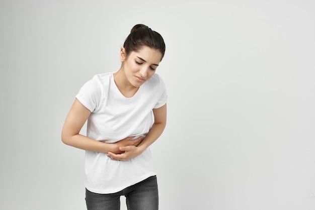 Frau im weißen t-shirt hält ihre bauchmenstruationsgesundheitsprobleme