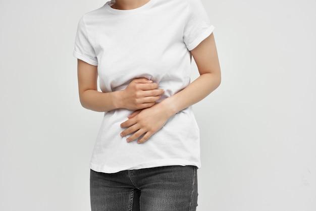 Frau im weißen t-shirt hält ihre magendurchfall-schmerz-gesundheitsprobleme. foto in hoher qualität