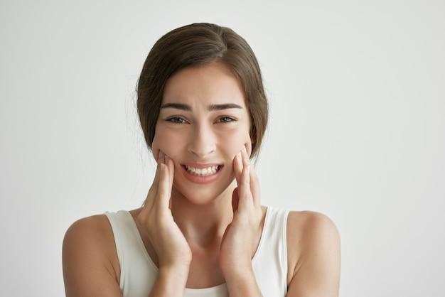 Frau im weißen t-shirt mit gesicht zahnschmerzen unzufriedenheit hautnah. foto in hoher qualität