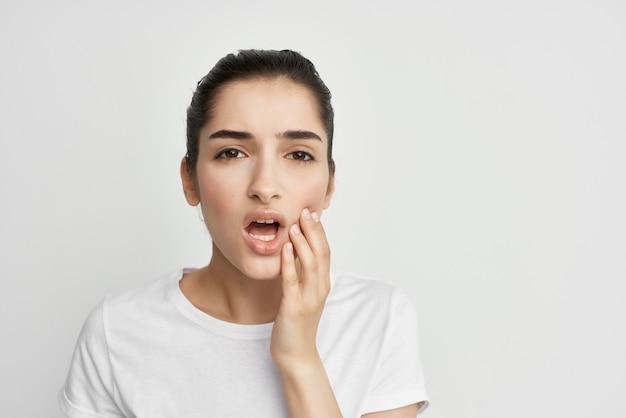 Frau im weißen t-shirt mit gesicht zahnschmerzen unzufriedenheit