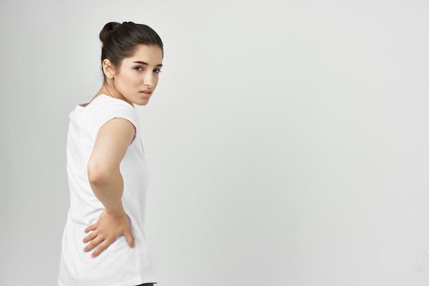Frau im weißen t-shirt mit rückenschmerzen im unteren rücken