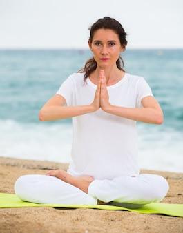 Frau im weißen t-shirt sitzt und übt meditation