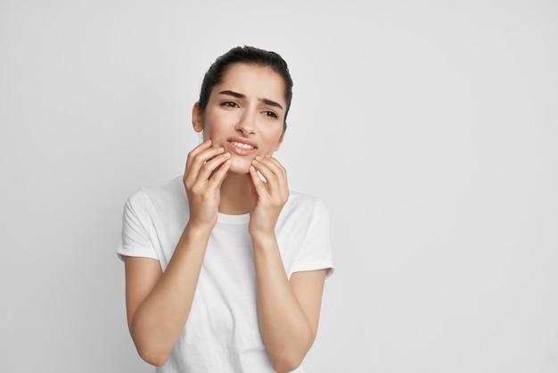 Frau im weißen t-shirt zahnschmerzen unbehagen nahaufnahme. foto in hoher qualität