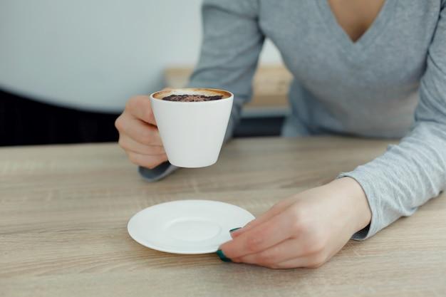 Frau im weißen tasse kaffee des grauen sweathergriffs