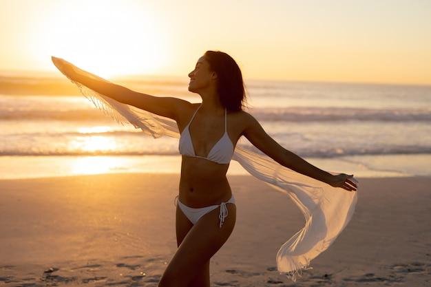Frau im wellenartig bewegenden schal des bikinis auf dem strand
