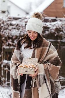 Frau im winter gekleidet hält box mit reisig russische traditionelle kekse hochwertiges foto