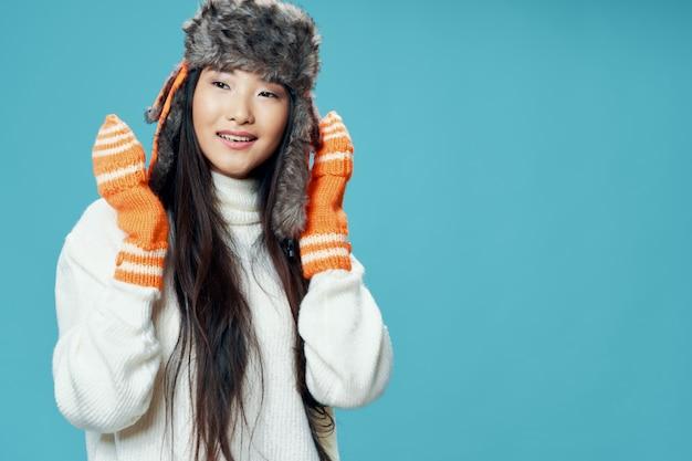 Frau im winterkleidung asiatisches aussehen kühle handschuhe wintermütze lebensstil eleganter stil blau