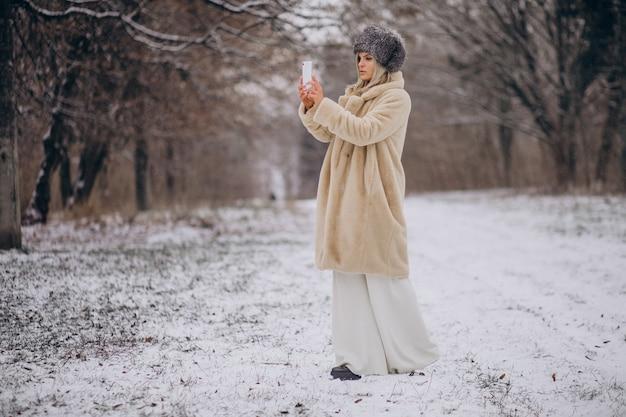 Frau im wintermantel, die im park voller schnee spaziert und am telefon spricht