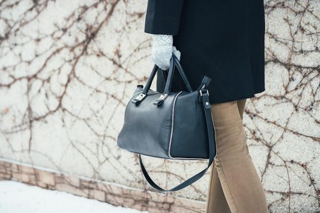 Frau im wintermantel gehend auf die straße mit handtaschen