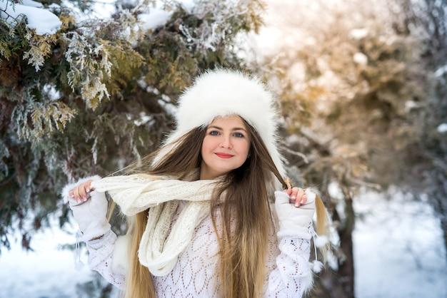Frau im winterpark, der in pelzmütze und schal aufwirft