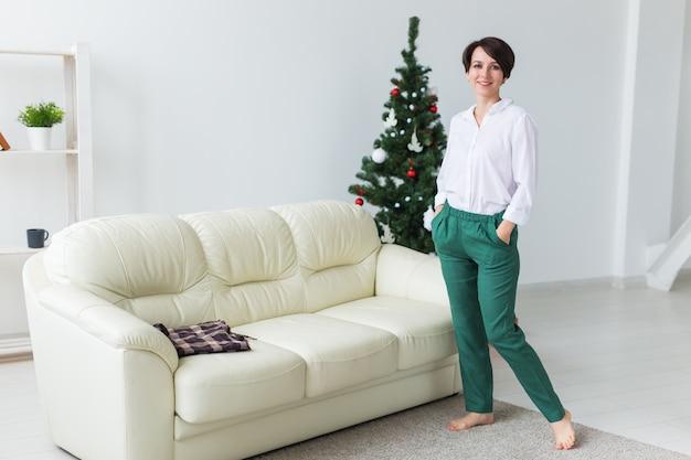Frau im wohnzimmer mit weihnachtsbaum