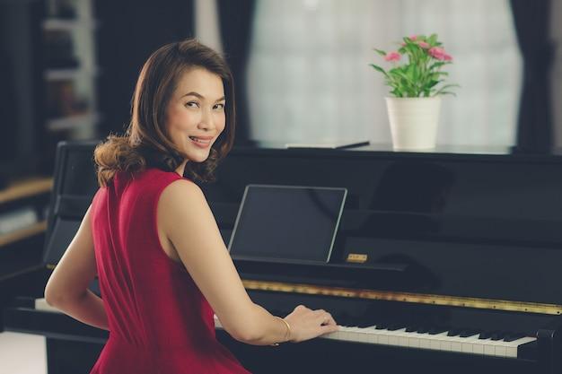 Frau im wohnzimmer zu hause sitzen lernen und lernen neue fähigkeiten, wie man klavier über online-klasse von einem tablet-computer spielt. prozess im film- und vintage-stil.