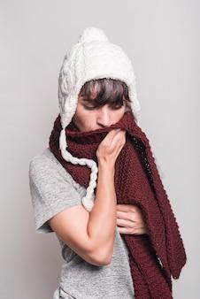Frau im wolligen hut, der ihren mund mit woolen schal gegen grauen hintergrund bedeckt
