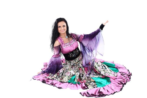 Frau im zigeunerkleid. volkstanz. weiße wand. das foto mit leerzeichen für text