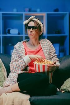 Frau in 3d-gläsern, die popcorn essen. lustige junge frau in den 3d-gläsern, die filmfilm ansehen, popcorn essen. menschen aufrichtige gefühle im kino