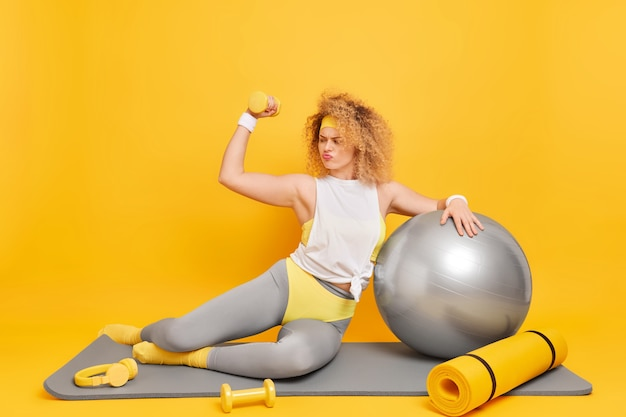 Frau in activewear hebt den arm mit hantel hat fitnesstrainingsposen auf der matte verwendet sportgeräte, die in guter körperlicher verfassung sind